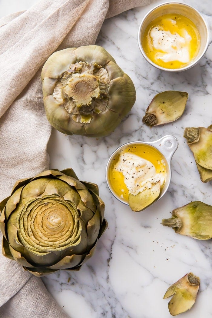 Two artichokes on a marble counter with bowls of dipping sauce