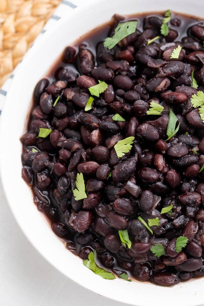 Overhead view of a partial view of a white bowl holding Instant Pot cooked black beans with garnish