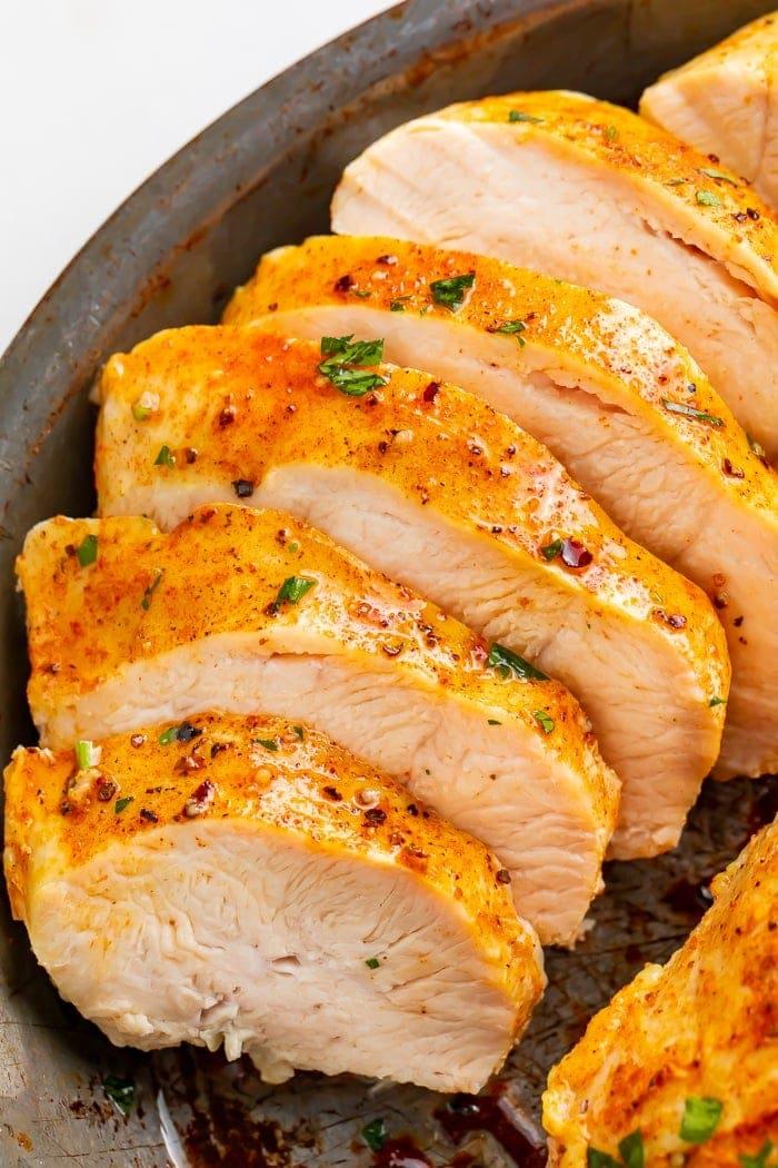 Sliced chicken breast on a dark plate
