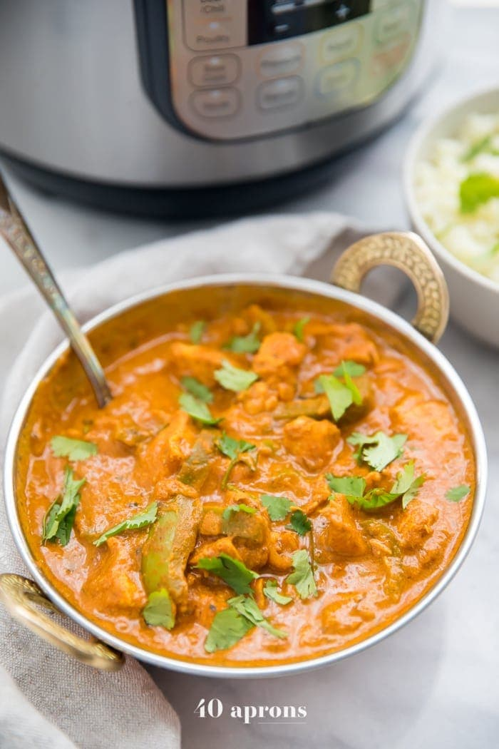 A bowl of chicken tikka masala in front of an Instant Pot