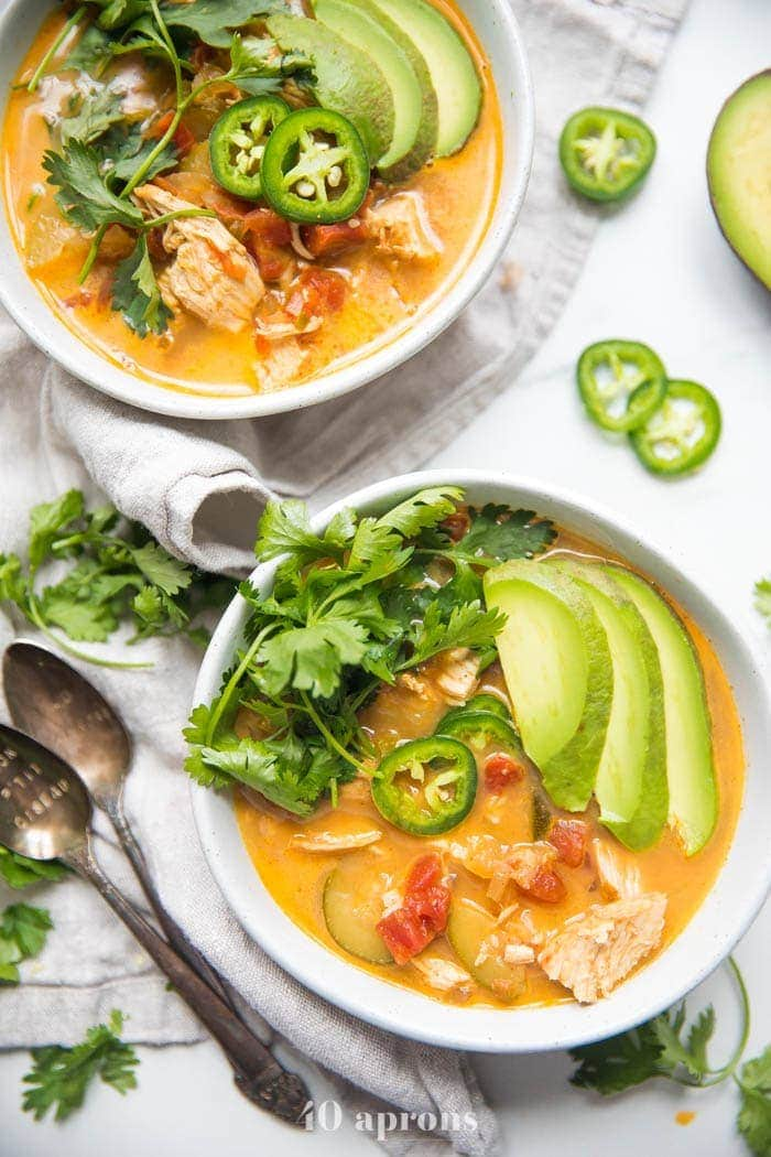 Overhead view of two bowls of low carb chicken tortilla-less soup with avocado garnish