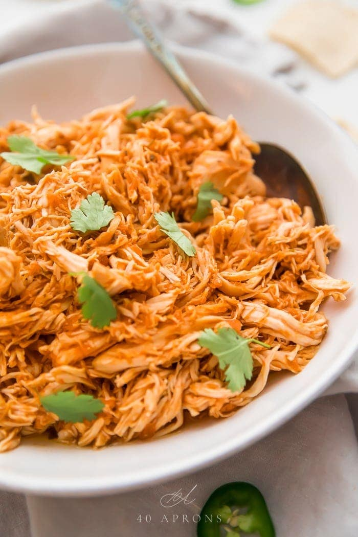 A white bowl of shredded Mexican chicken