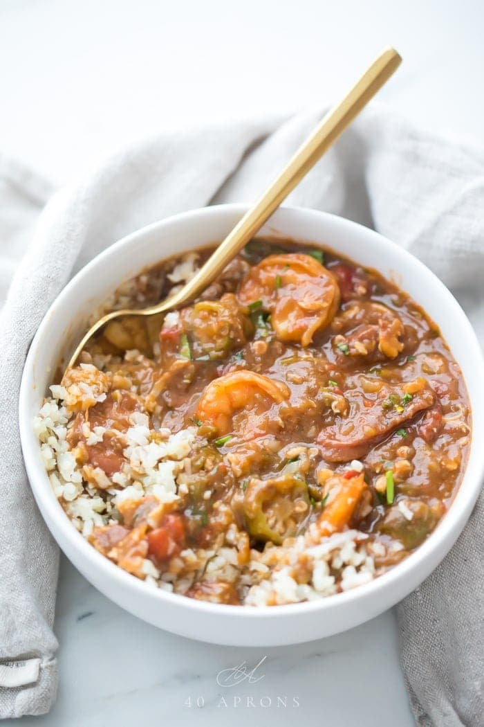 A bowl of crab, shrimp, and sausage seafood gumbo with white rice on a light napkin