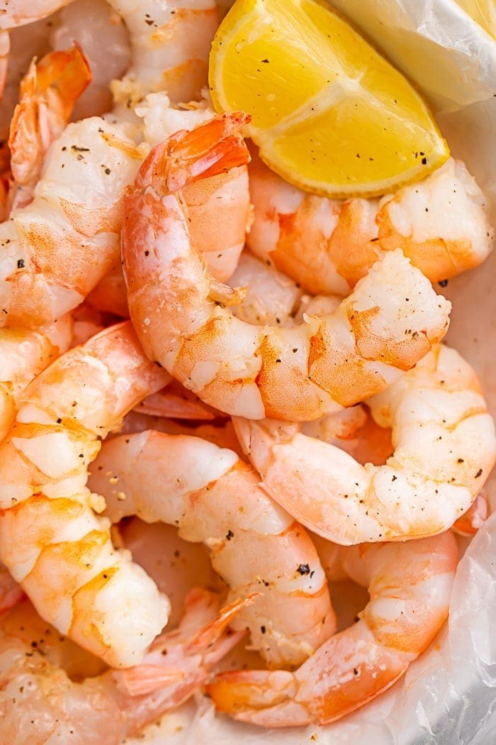 Closeup of cooked shrimp in a bowl with a lemon wedge