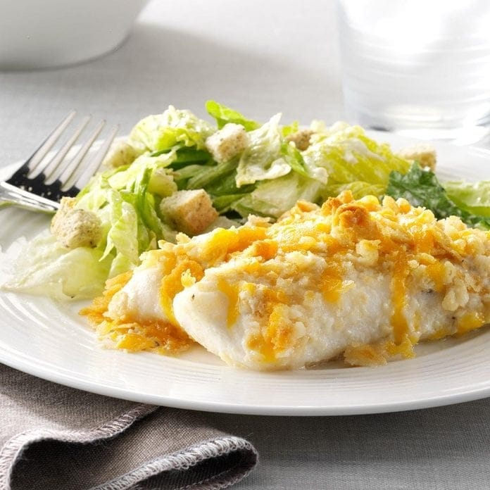 Fish and caesar salad on a white plate