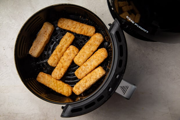 Frozen fish sticks in a black air fryer basket