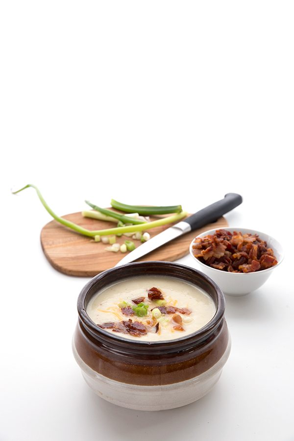 Bowl of cauliflower soup in front of bowls of garnish against a white backdrop