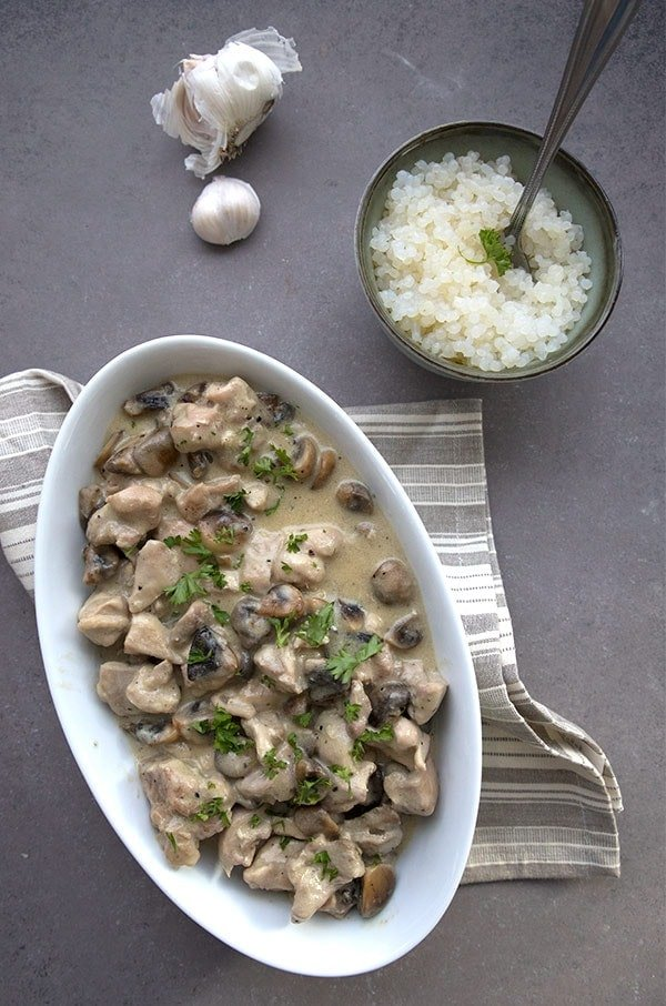 A white boat dish with chicken and mushrooms on a dark countertop