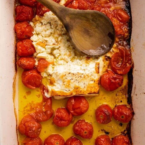 Baked feta and tomatoes smushed in oil in a large pan with a wooden spoon