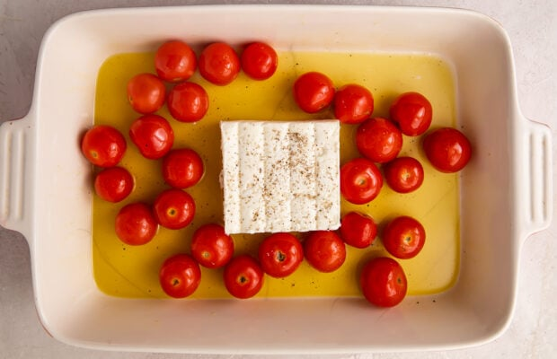 Cherry tomatoes and feta in a pool of olive oil in a rectangular baking dish