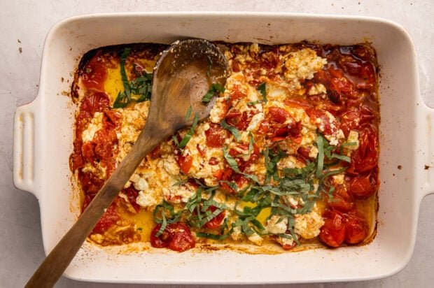 Baked feta and tomatoes, mashed together, with basil and olive oil in a casserole dish, with a wooden spoon laid across diagonally