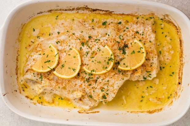 Baked fish topped with parsley and lemon slices in a white baking dish