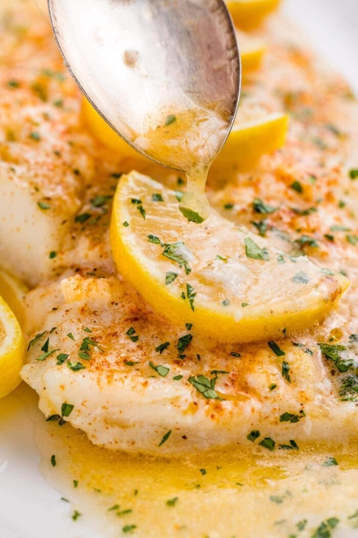A close up of lemon garlic butter spooned over baked fish