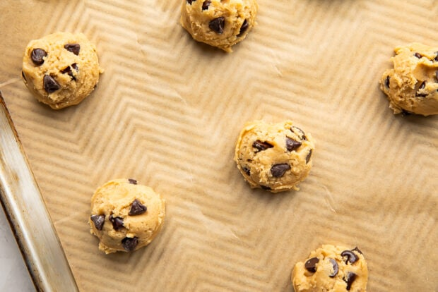Cookie dough balls on a baking sheet lined with parchment paper