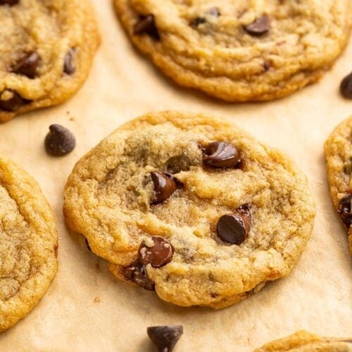Angled view of vegan chocolate chip cookies on parchment paper