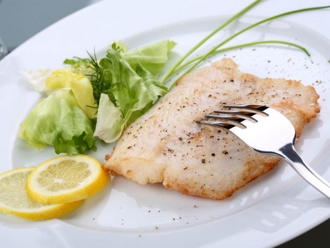 Grilled orange roughy on a white plate with lemon slices and a small salad
