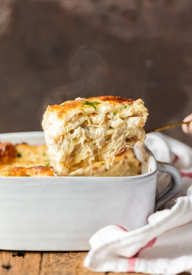 A square piece of seafood lasagna being lifted out of a white casserole dish with a spatula