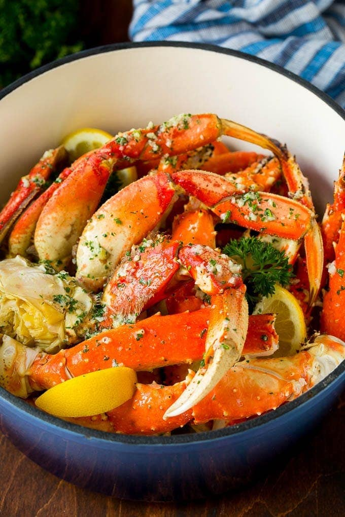 A big pot of bright red crab legs with yellow lemon wedges