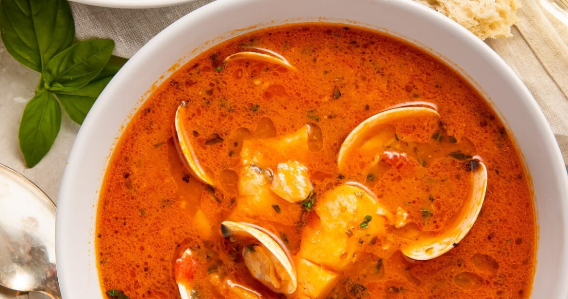 Two bowls of red Italian fish stew on a table surrounded by pieces of bread