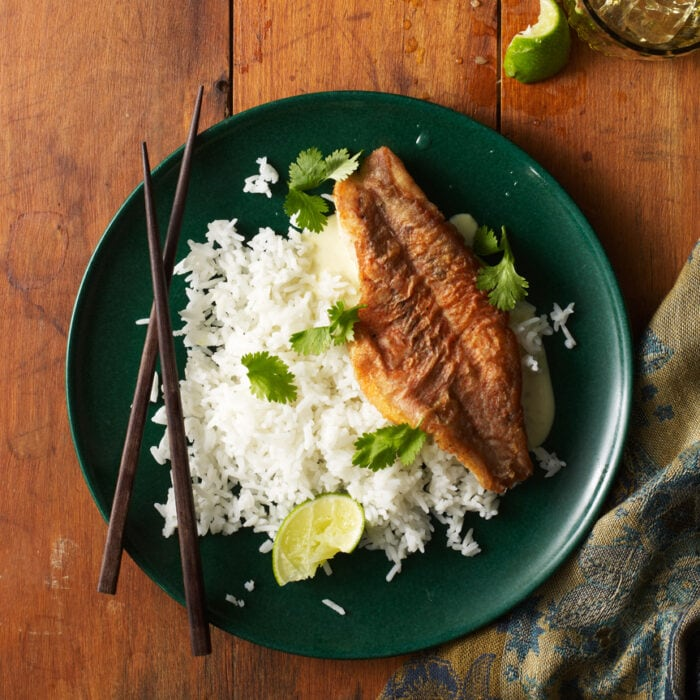 Orange roughy and white rice on a green plate with chopsticks