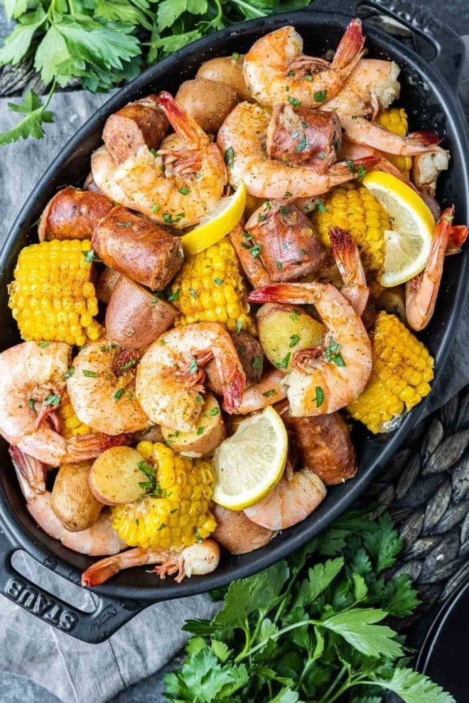Instant Pot shrimp boil - shrimp, potatoes, corn, lemon on a black platter
