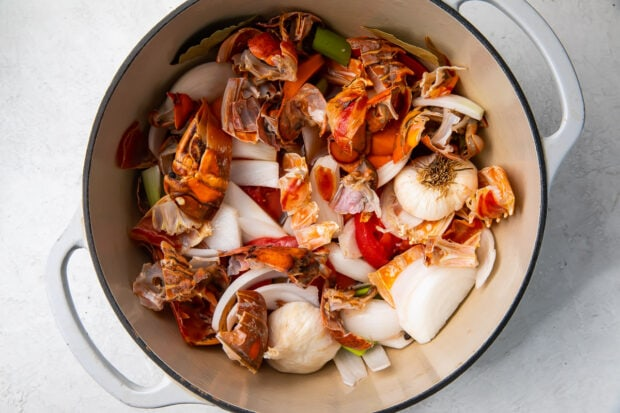 Lobster shells, onion, garlic, and vegetables in a large pot