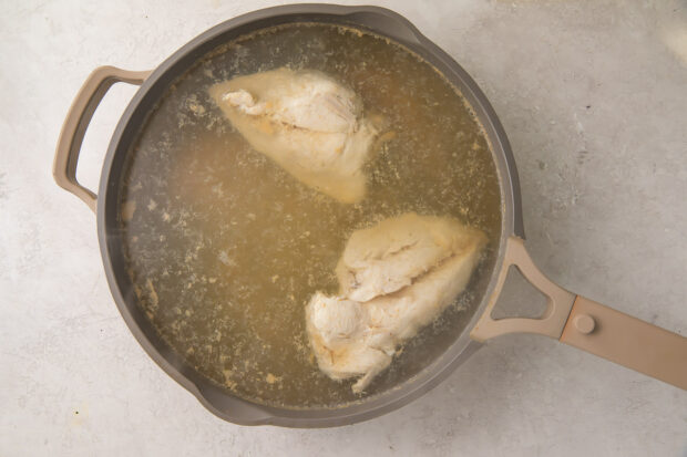 Cooked chicken breasts in chicken stock in a silver skillet