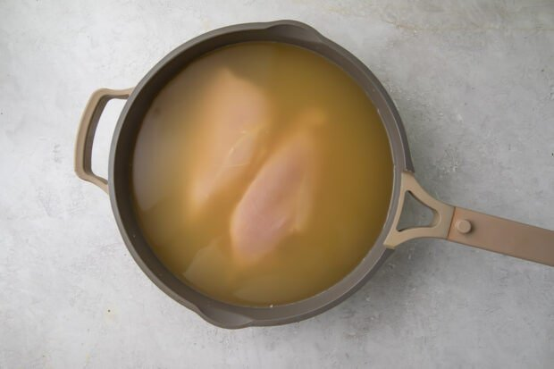 Chicken breasts covered with chicken stock in a large skillet