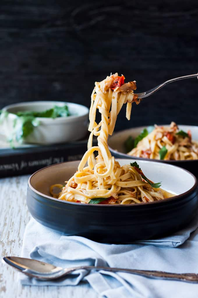 Venetian crab linguine in a dark bowl with a white interior, being lifted in the air on a fork