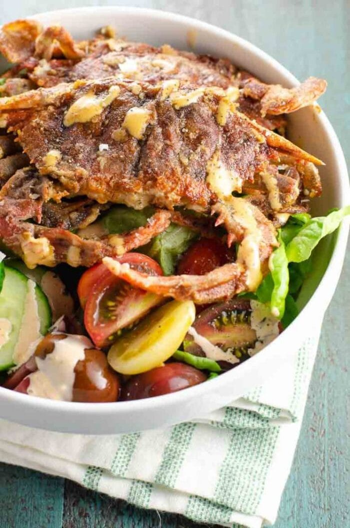 Fried soft shell crab on a salad in a large white bowl