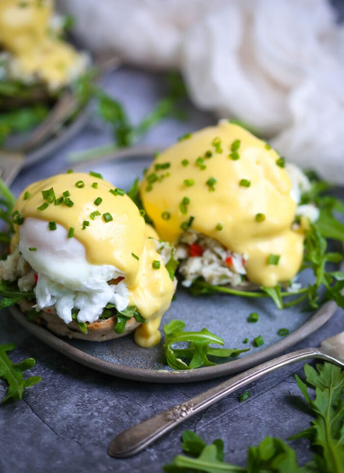 Two eggs benedict on a blue plate with grey trim