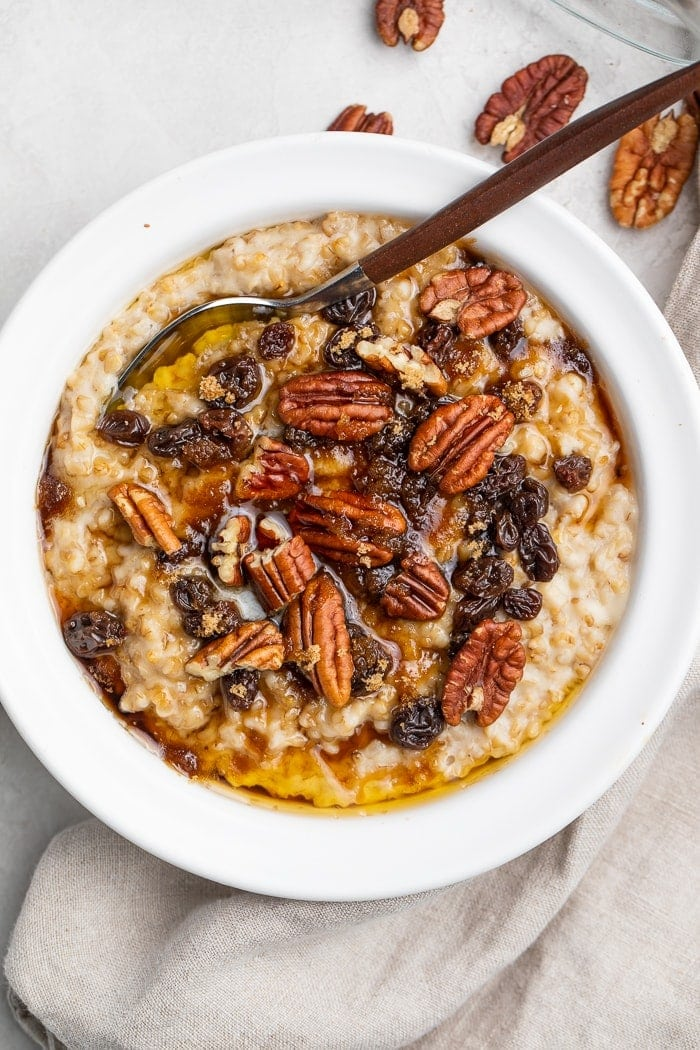 Instant Pot steel cut oats in a white bowl, topped with pecans