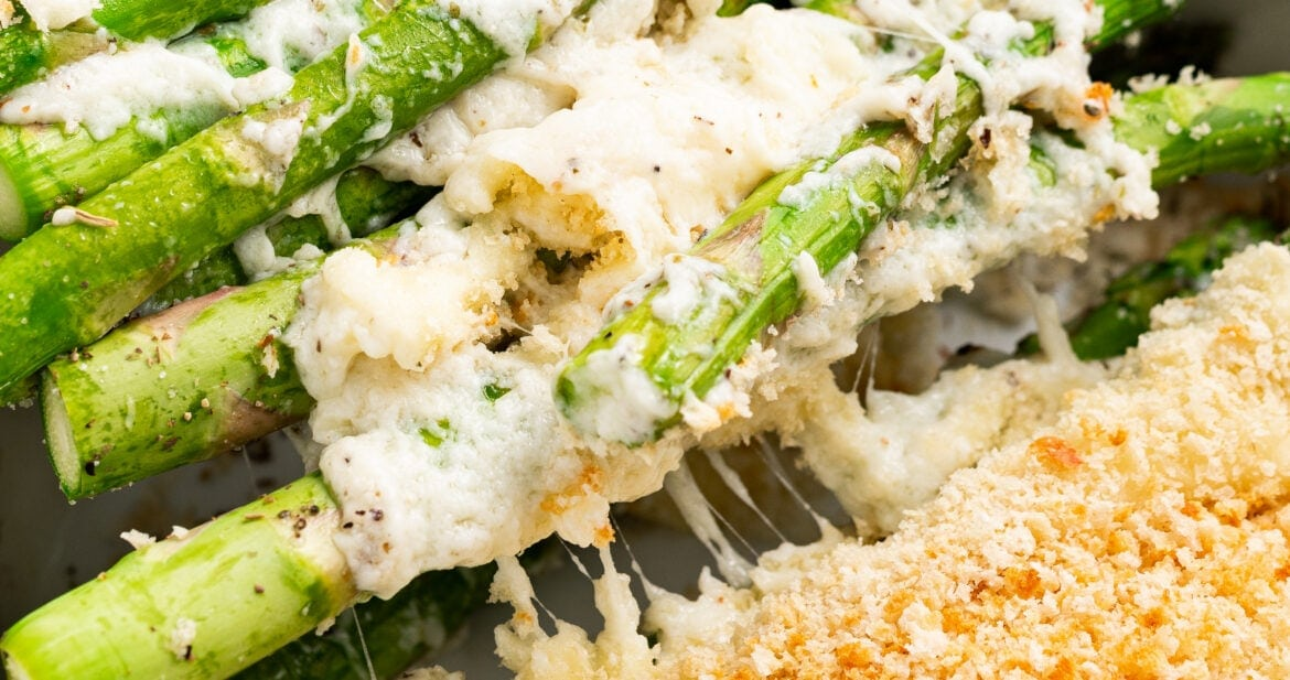 Asparagus casserole being scooped out of the baking dish with a spatula.