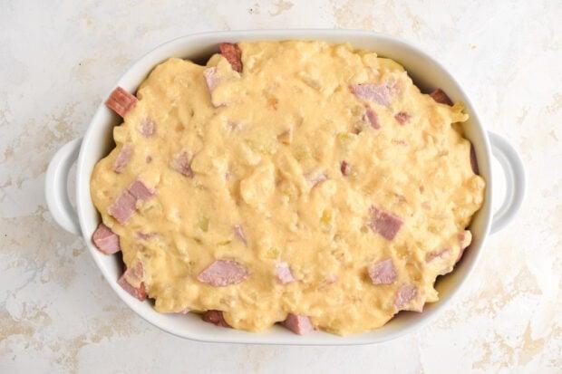 Cheesy potato and ham casserole, uncooked, in a white casserole dish