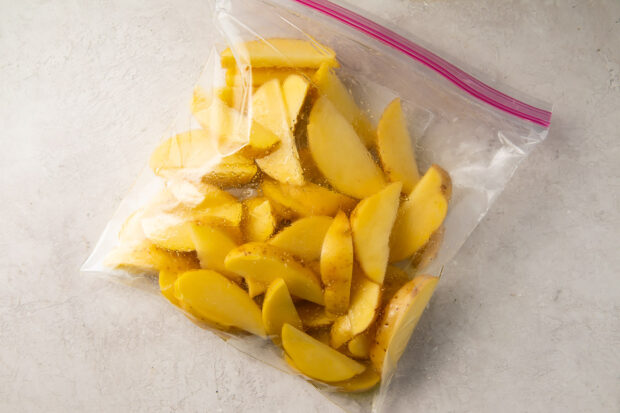 Raw potato wedges and olive oil in a plastic bag