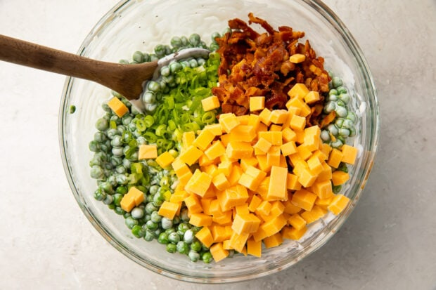 Peas, cheddar, scallions, and bacon in a large glass mixing bowl with a wooden spoon