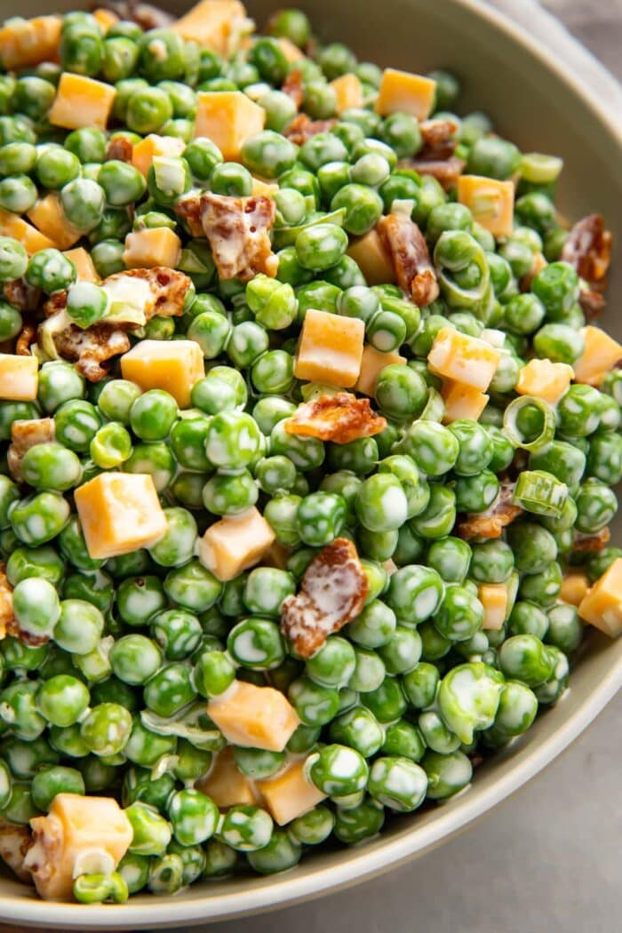 Pea salad with bacon, cheddar, and green onions in a large bowl