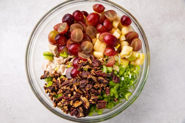 Ingredients for chicken salad with grapes and pecans in a glass mixing bowl