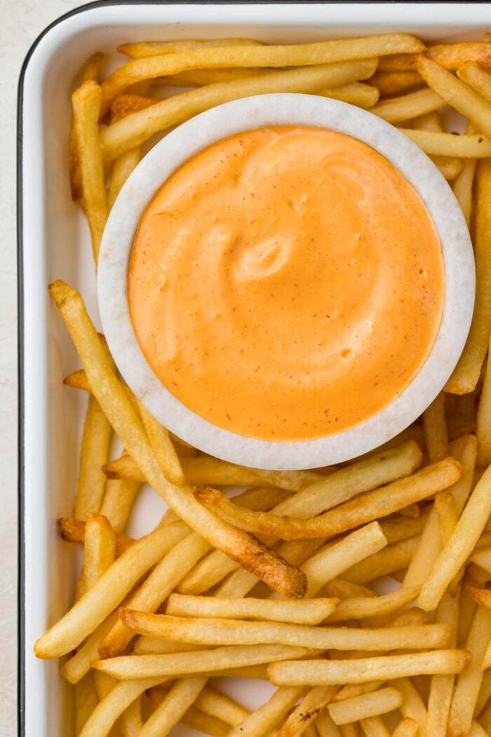 A small marble bowl of chipotle aioli surrounded by french fries on a baking sheet