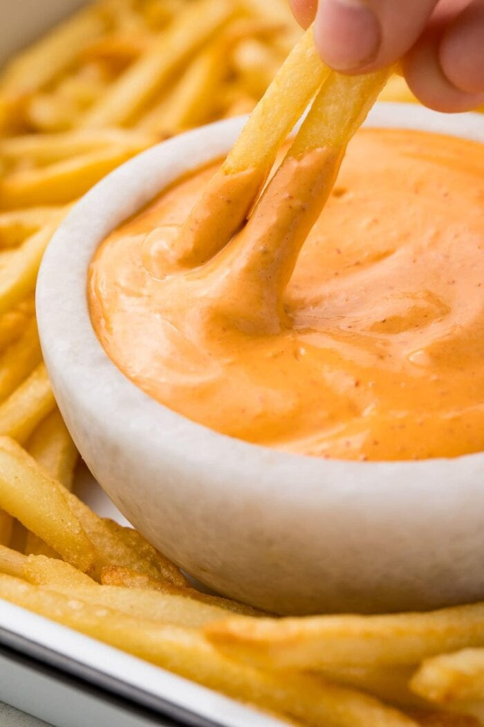 Two french fries dipped in chipotle aioli in a small bowl