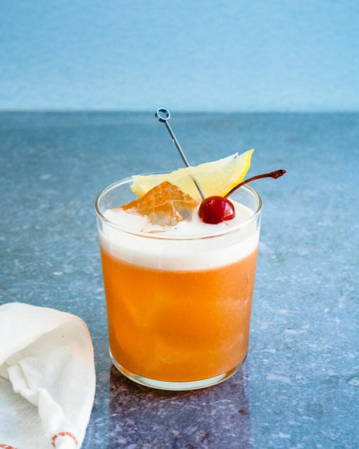 A classic amaretto sour with an egg white foam and cherry garnish