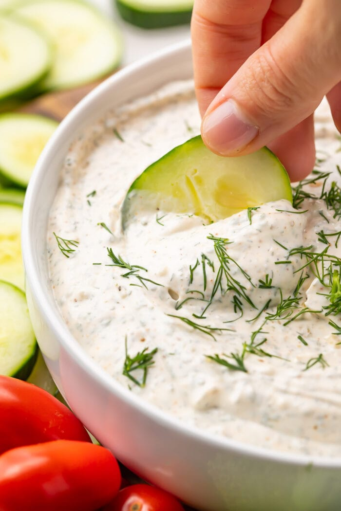 Cucumber dipped into a bowl of dill dip