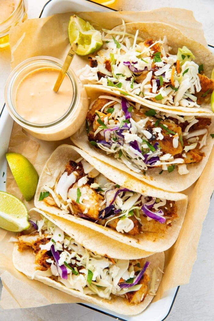 4 fish tacos lined up on a platter next to a glass jar of fish taco sauce