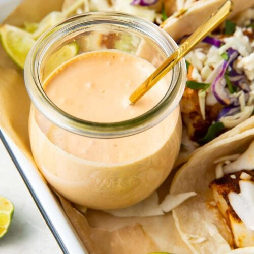 Fish taco sauce in a glass jar with a spoon