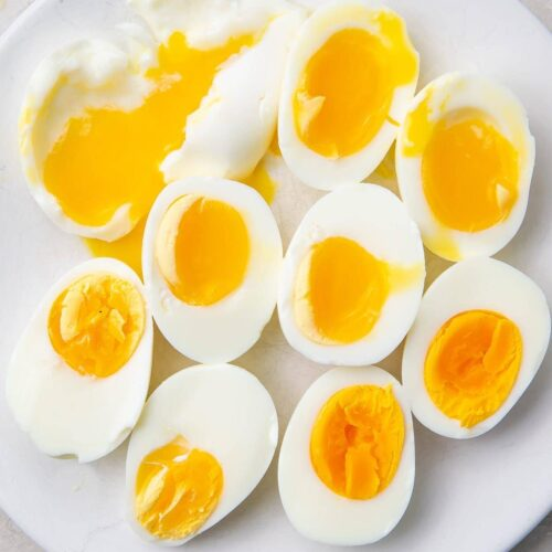 Various halved Instant Pot eggs on a white plate