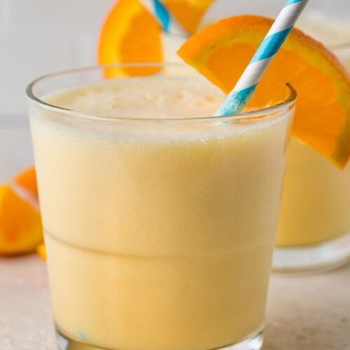 Short glass containing a serving of Orange Julius with an orange slice and a blue and white striped straw