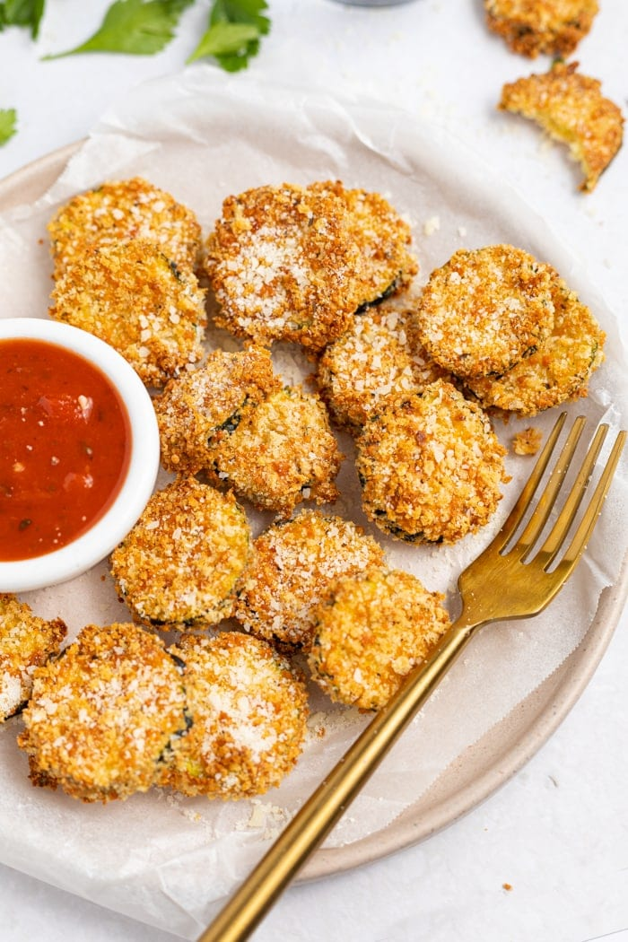 Air Fryer Zucchini Chips on a plate, sprinkled with parmesan cheese and served with marinara sauce.