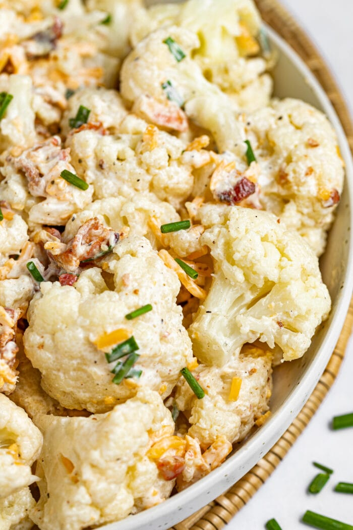 Cauliflower salad in a bowl with chives sprinkled on and around the bowl.