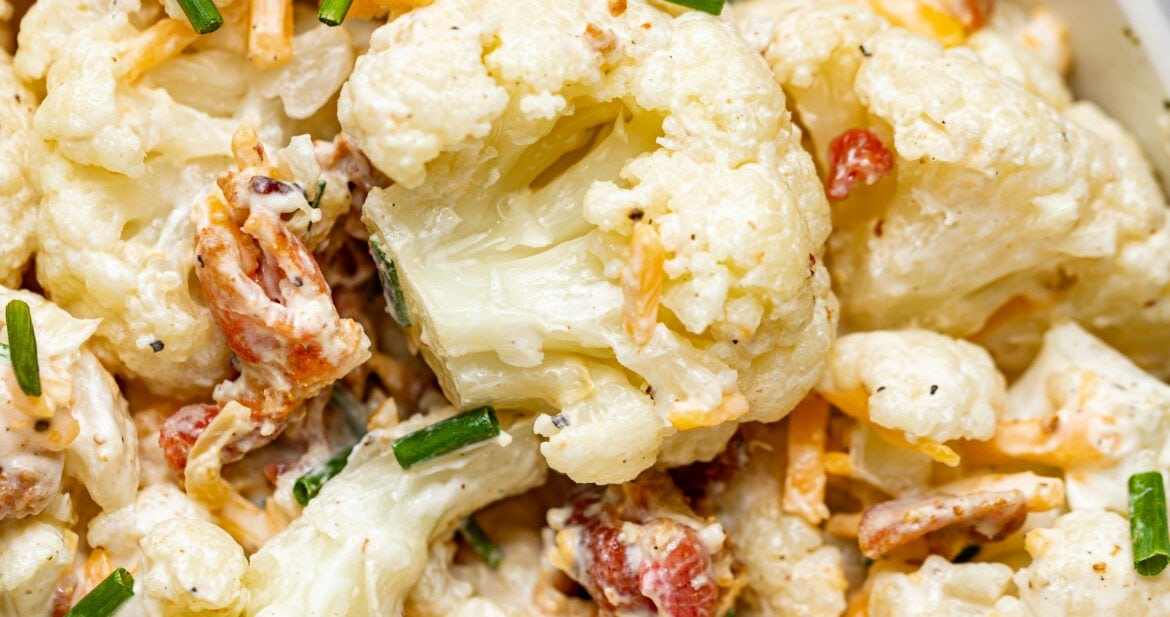 Close up image of cauliflower salad in a bowl with chives sprinkled on top and a lemon on the side.