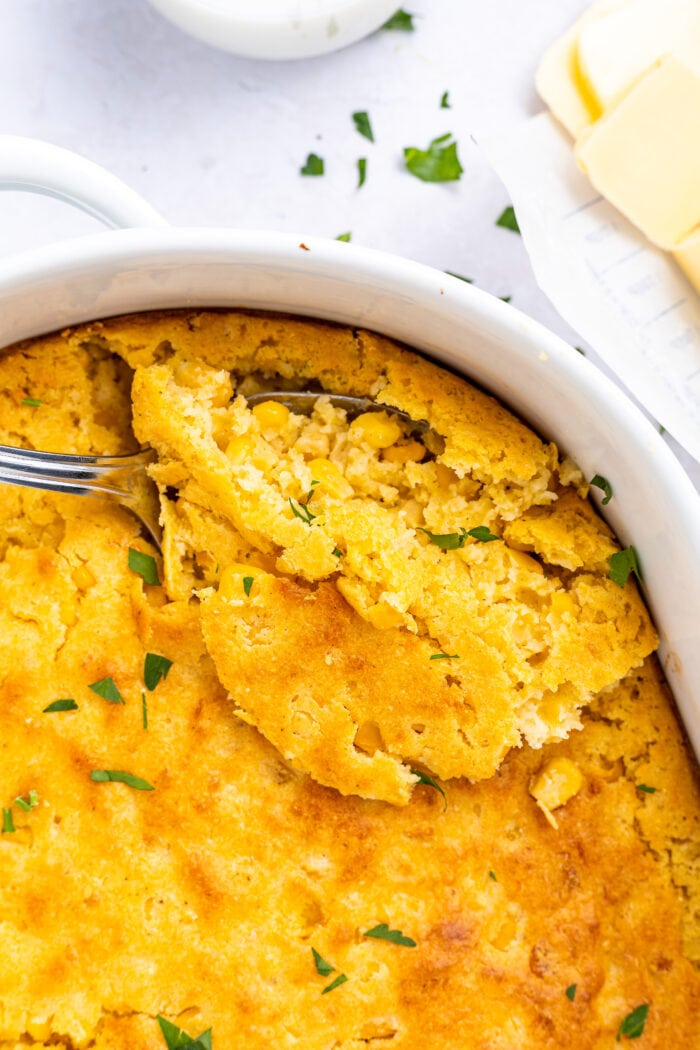 Overhead image on cornbread casserole being scooped out of baking dish with sliced butter on the side.